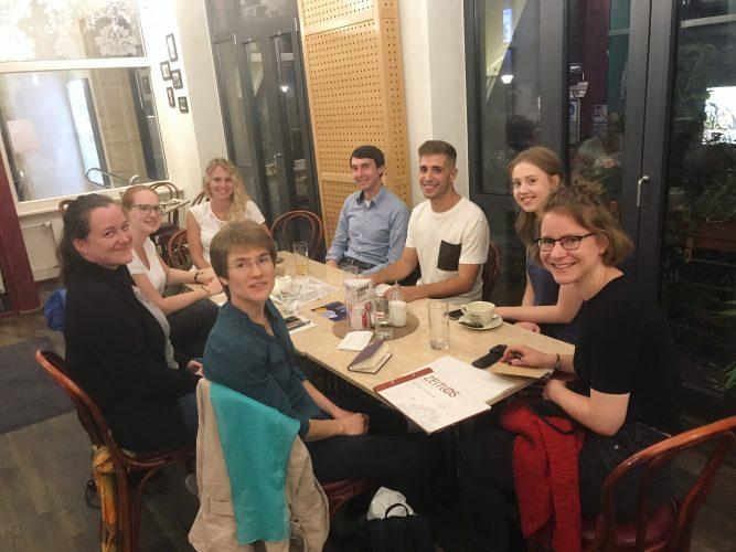 Foto: Acht junge Menschen sitzen um einen Tisch. Vor ihnen liegen Arbeitsunterlagen.