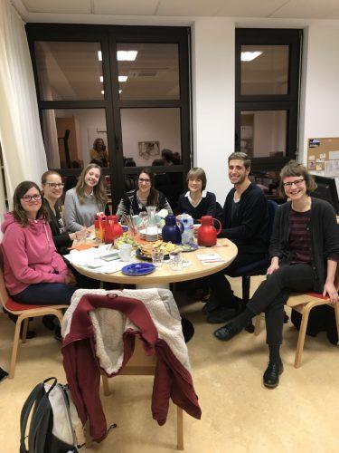 Eine Gruppe junger Menschen sitzt um einen Tisch und lächelt in die Kamera