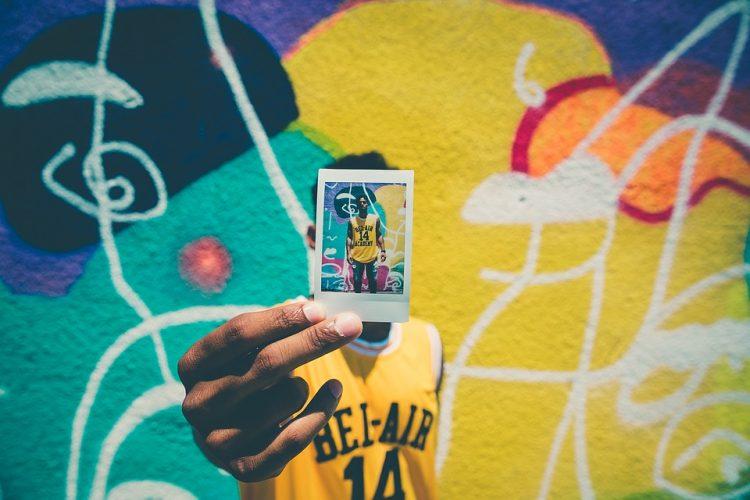 Eine Person hält ein Polaroid Foto von sich in die Kamera