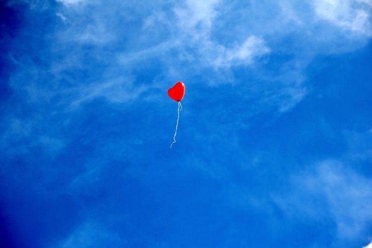 ein roter Herzluftballon steigt in den Himmel
