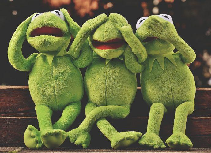 Drei Frösche aus Plüsch sitzen nebeneinander und stellen nicht hören, nciht sehen, nicht sprechen dar.